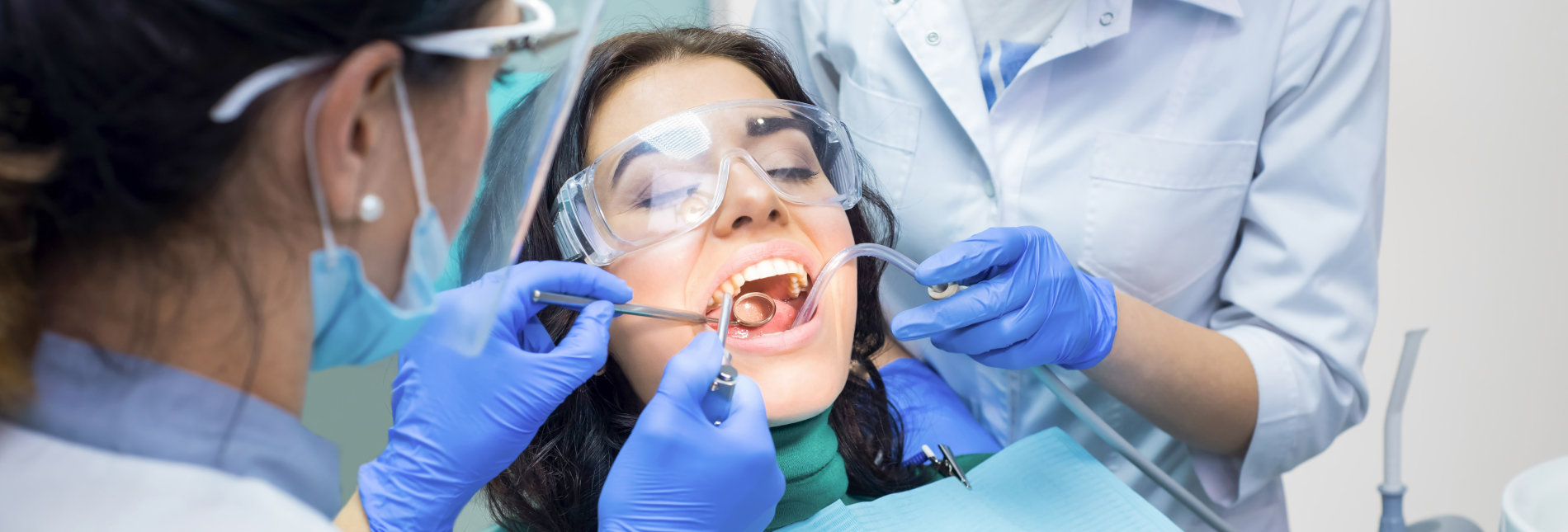 Two dental doctors and patient. Procedure at the dentist office.